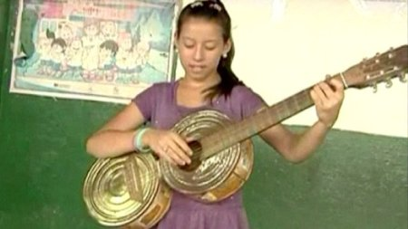 Ein Paraguayanisches Mädchen spielt auf einem Abfall-Instrument. Bild BBC News.