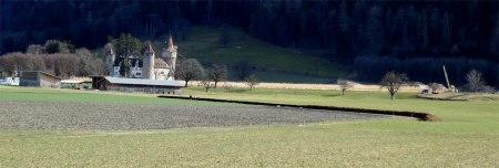 """Langer Misthaufen mit Abdeckvlies daneben. Stallbau ohne Mistplatte. """"Über"""" dem alten Mistlager im Dorf steht jetzt ein Mehrfamilienhaus. Im Hintergrund Schloss Marchlins links, rechts Kiesgrube."""
