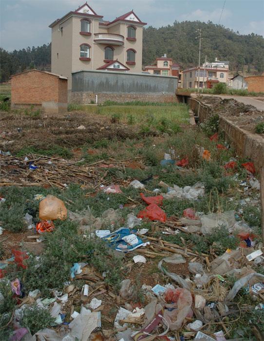 ... Häuser verdrängen Felder, Abfall gelangt in den Boden. Copyright Martin X. ...