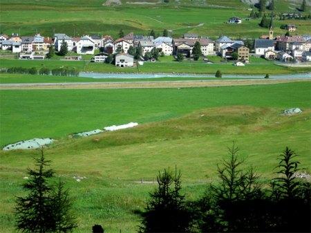 Drei Misthaufen (und Siloballen), im Hintergrund der Inn und das Dorf S-chanf. Copyright Theo.