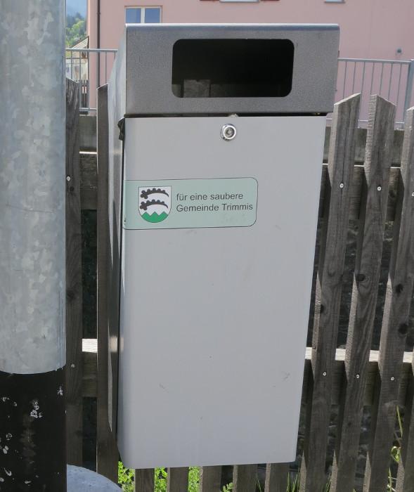 """Neben dem Dorfbach ein Abfallkübel mit der Aufschrift: """"für eine saubere Gemeinde Trimmis"""". Klara: <em>""""Da müssten sie aber bei den Bauern genauer hinschauen!""""</em> Heidi: <em>""""Ja, die Gemeinden nehmen die Neubauten ab, mit geschlossenen Augen. Es gibt welche, die merken nicht einmal, wenn die Mistplatte fehlt oder Abwasser in einen Bach fliesst. Subventionen werden deswegen kaum gekürzt, wenigstens im Kanton Graubünden nicht.""""</em>"""