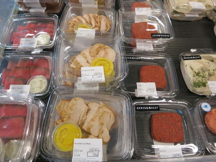 """Die täglichen Versuchungen am Eingang eines COOP-Ladens: Fleisch, """"hausgemacht"""" verarbeitet, in viel Wegwerfplastik verpackt ..."""