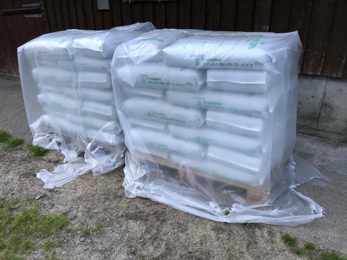 2 x 21 Säcke mit Dünger vor einem Alpstall. Copyright: Janik