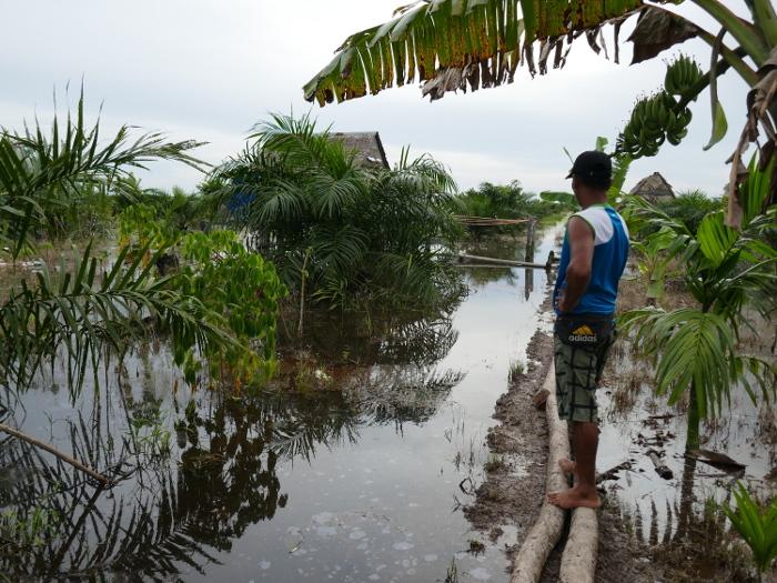 Ein Kleinbauer betrachtet sein überflutetes Feld. Copyright: Jennifer Merten